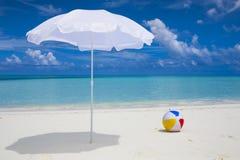 weißer Sonnenschutz und Kugel am Strand Lizenzfreies Stockfoto
