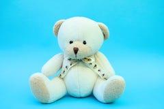 Weißer Spielzeugteddybär betreffen blauen Hintergrund lizenzfreie stockfotografie