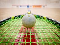Weißer Squashball auf den Schnüren eines Schlägers mitten in a Stockbilder