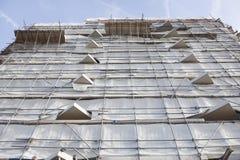 Weißer Stoff auf Baugerüst des hohen Neubaus und des blauen Himmels Lizenzfreie Stockfotografie