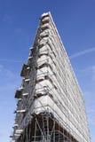Weißer Stoff auf Baugerüst des hohen Neubaus und des blauen Himmels Stockbilder