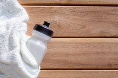 weißer Stoff der Draufsicht und Plastikwasserflasche auf Holztisch Stockbilder