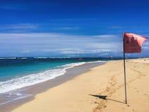Weißer Strand mit roter Fahne und vervollkommnen blauen See- und des freien Raumesblauen Himmel Lizenzfreie Stockbilder