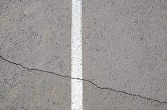 Weißer Streifen auf gebrochenem Asphalt Lizenzfreie Stockfotos