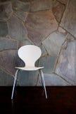 Weißer Stuhl durch Steinwand Stockfotos