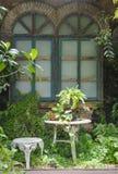 Weißer Stuhl und schöne Weinlesefensterrahmen im Häuschen arbeiten im Garten lizenzfreie stockfotos