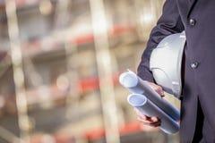 Weißer Sturzhelm und Pläne auf Baustelle Stockfoto