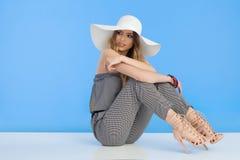 Weißer Sun Hut schönes Mode-Modell-In Jumpsuit Ands ist, schauend sitzend und weg über Schulter Stockbild