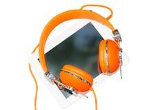 Weißer Tablet-Computer mit den orange Kopfhörern lokalisiert auf Weiß Stockfotografie