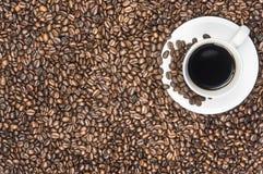 Weißer Tasse Kaffee auf Bohnen Lizenzfreie Stockfotografie