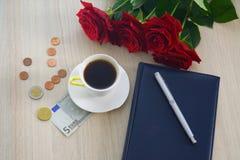 Weißer Tasse Kaffee auf dem Tisch, mit Rosen, Stift und Geld Stockbilder