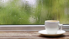 Weißer Tasse Kaffee auf hölzernem Fensterbrett oder Tabelle der Weinlese gegen Fenster mit Regentropfen und Laub auf unscharfem H stock footage