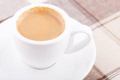 Weißer Tasse Kaffee auf Tischdecke Stockfotografie