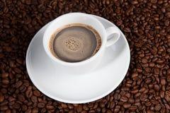 Weißer Tasse Kaffee an den Kaffeebohnehintergründen Lizenzfreies Stockbild