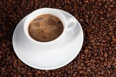 Weißer Tasse Kaffee an den Kaffeebohnehintergründen Lizenzfreie Stockfotos
