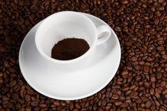 Weißer Tasse Kaffee an den Kaffeebohnehintergründen Stockbild