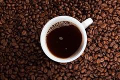 Weißer Tasse Kaffee an den Kaffeebohnehintergründen Lizenzfreie Stockfotografie