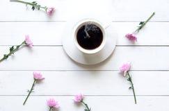 Weißer Tasse Kaffee mit rosa Blume am weißen sonnigen Tag des Holztischs morgens Stockbild