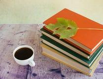 Weißer Tasse Kaffee nahe bei den mehrfarbigen Büchern Lizenzfreie Stockfotografie