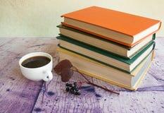 Weißer Tasse Kaffee nahe bei den mehrfarbigen Büchern Stockfotos