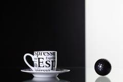 Weißer Tasse Kaffee und schwarzer Golfball Stockbilder