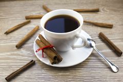 Weißer Tasse Kaffee und Zimt auf einem hölzernen Hintergrundkaffee stockfotografie