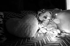 Weißer Teddybär betreffen Couch mit feenhaften Lichtern lizenzfreie stockbilder