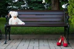Weißer Teddybär betreffen eine Holzbank im Park Stockfotografie
