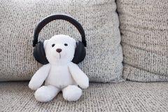Weißer Teddybär des Lächelns, der auf Sofa und tragendem Kopfhörer sitzt Lizenzfreies Stockbild