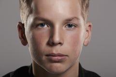 Weißer Teenager, der oben zur Kamera, Abschluss, horizontal schaut Stockfotografie