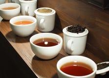 Weißer Teetopf und -schalen mit den schwarzen Teeblättern Stockfotos