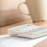Weißer Tischrechner auf einem Dokument nahe bei einem Becher Lizenzfreies Stockbild