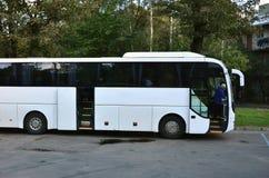 Weißer Touristenbus für Exkursionen Der Bus wird in einem Parkplatz nahe dem Park geparkt lizenzfreies stockbild