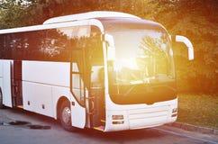 Weißer Touristenbus für Exkursionen Der Bus wird in einem Parkplatz nahe dem Park geparkt lizenzfreie stockfotos