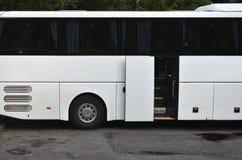Weißer Touristenbus für Exkursionen Der Bus wird in einem Parkplatz nahe dem Park geparkt lizenzfreie stockfotografie