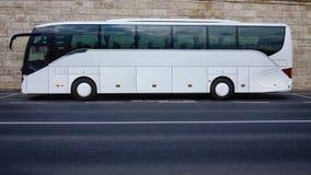 Weißer Touristenbus geparkt auf leerer Straße Lizenzfreies Stockfoto
