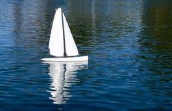 Weißer Toy Sailboat auf einem blauen Teich Lizenzfreie Stockfotos