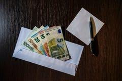 Weißer Umschlag mit Eurorechnungen Stockfotografie