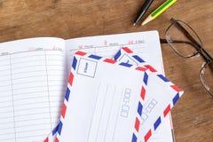 Weißer Umschlag, pencels, Notizbuch und Gläser auf einem Holzfußboden Stockbilder