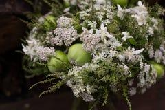 Weißer und grüner Blumenstrauß mit Blumen und Äpfeln Stockfoto
