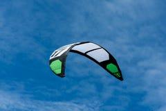 Weißer und grüner kitesurfing schleppender Drachen in der Luft stockfotografie