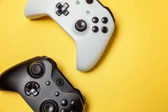 Weißer und schwarzer Steuerknüppel zwei auf gelbem Hintergrund Computerspielwettbewerbsvideospielsteuerkonfrontationskonzept stockbilder