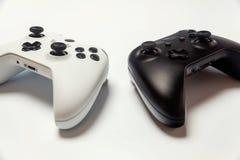 Weißer und schwarzer Steuerknüppel zwei auf weißem Hintergrund Computerspieltechnologiespielwettbewerbsvideospielsteuerkonfrontat stockfotografie