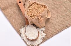 Weißer ungeschälter Reis auf hölzernem Löffel und Hanfsack mit braunem Samen des ungeschälten Reises auf weißem Hintergrund Lizenzfreie Stockfotografie