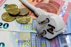 Weißer Verbindungsstecker und Eurobanknoten und -münzen als Hintergrund stockfotografie