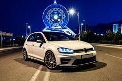 Weißer VW spielen am Abend nahe bei dem Riesenrad Golf Ansicht von der Ecke stockfotos