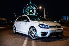 Weißer VW spielen am Abend nahe bei dem Riesenrad Golf Ansicht von der Ecke lizenzfreies stockbild