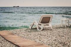 Weißer Wagenaufenthaltsraum auf einem Strand von Kieseln Lizenzfreie Stockbilder
