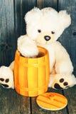 Weißer weicher Teddybär betreffen einen hölzernen Hintergrund stockbild