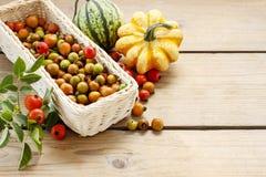Weißer Weidenkorb der Hagebutte trägt auf Holztisch Früchte Stockfoto